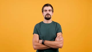 Handsome man in casual t-shirt sweating from hot weather isolated on yellow orange background