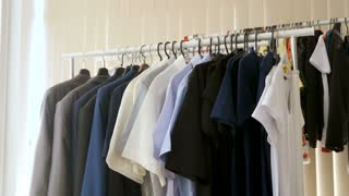 Hanger full of business suits, shirts and t shirts in a shop