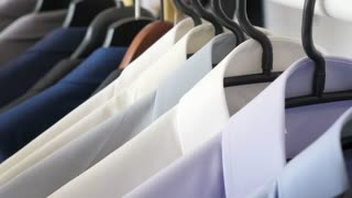 Hanger with male busines suits and shirt. Close up dolly footage