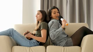 Happy and positive sisters playing and singing on the sofa in the living room. The youngest is playing at ukulele while the oldest is singing in a microphone. They are sitting on the couch with their