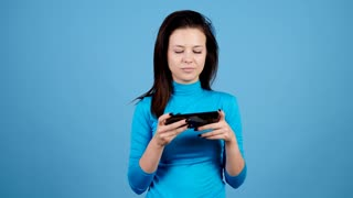 Happy casual woman plays video games on her smartphone on blue background. Leisure, entertainment and fun