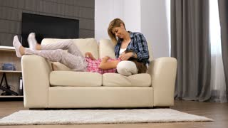 Happy mother and teenage daughter tickling each other. At the end the daughter falls on the floor and laughs