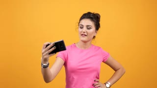 Happy smiling woman in pink t-shirt taking a selfie on yellow orange background