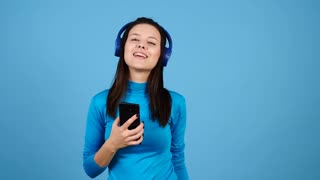Happy woman wearing headphones and singing in her smartphone on blue background. Beautiful girl dancing and having fun. Slow motion footage