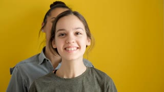 Happy younger and oldest sisters dancing and laughing on yellow background. Slow motion footage