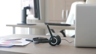Headphones lying on the desk in customer care support office. Telemarketing or customer support line