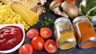 Healthy and delicious dinner ingredients on dark table. Variety of pasta and spaghetti. Dolly slide footage