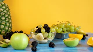 Healthy and organic fruit salad made of bananas, kiwi, grapes and berries on yellow backgorund. Parallax dolly footage