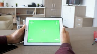 Holding a digital tablet PC in hands with green screen chroma mock up on desk in living room house. Dolly slider 4K footage with parallax effect