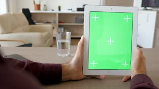 Holding a digital tablet PC in vertical position with green screen chroma mock up at the table in the living room of the house. Dolly slider 4K footage with parallax effect