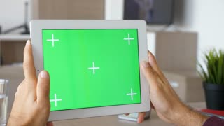 Holding a digital tablet PC with green screen mock-up in hands in horizontal mode. Markers available for tracking