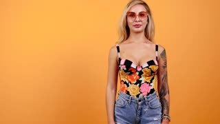 Hot sexy tattooed woman dances in slow motion on yellow orange background then she blowes kisses to the camera