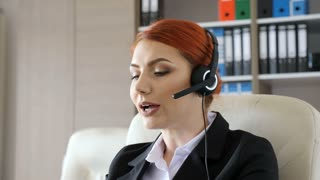 Hotline worker at her desk looking in the laptop and speaking through headset. Customer care and help line