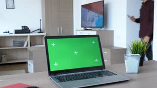 In a moder apartment a laptop with green screen mock-up sits on the table. A person is walking in the room and sits on the couch while the TV is on