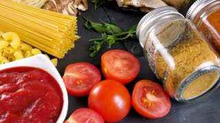 Ingredients for dinner preparation on dark table. There are different types of pasta and other food ingredients. Dolly slide footage