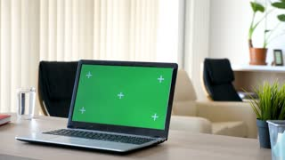 Laptop on a desk in the living room with a isolated green screen and marks for tracking. Man walks in the room and sits on the couch in the background