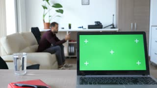 Laptop with green screen chroma on it in the middle of living room. The screen is with markers for traking. Dolly slider 4K footage