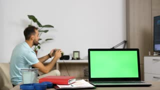 Laptop with green screen on the table in the living room while a man in background is watching TV and a woman at the desk is making a phone call. Dolly slider 4K footage