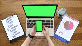 Male hands scrolling and touching a phone display with green screen next to a laptop with chroma also. Top view footage