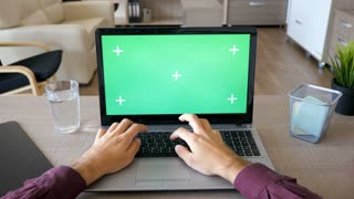 Male hands typing on the laptop keyboard with chroma green screen mock up in his house. POV footage of person typing