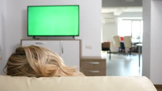 Man and woman cozy on the couch watch a TV with green screen. Dolly slider 4K footage