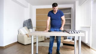 Man assembling furniture in new house where he and his wife just moved in. There are cardboard boxes all over the place