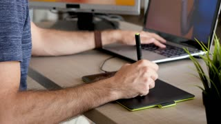 Man hand drawing using a digital tablet ot his desk. Creative professional. Close up footage