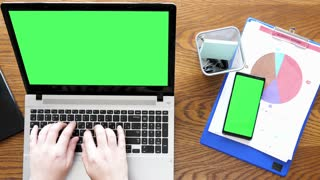 Man hands typing on a laptop with green screen then touching a green screen display on a smartphone. Top view dolly footage