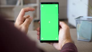 Man holding a smartphone in hands with green screen chroma mock up at his desk in the house