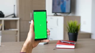 Man holds in hand a modern smartphone with green screen chroma mock up over a blurred living room background