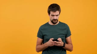 Man in casual t-shirt typing and browing on his smartphone isolated on yellow orange backrground in studio. Persona holding a tech device in hands