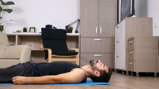 Man lying down on a blue mat on his living room, relaxing after a yoga session. Dolly slider 4K footage