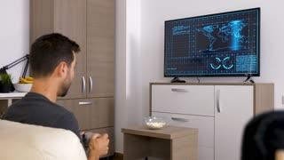 Man playing a strategic video game on the console on big screen TV. Back view. Dolly slider 4K footage