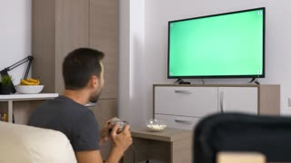 Man playing a video game on the console in front of green mock-up screen on big plasma TV. Dolly slider 4K footage