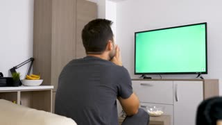 Man watching a big green mock-up screen TV in the living room. 4K footage