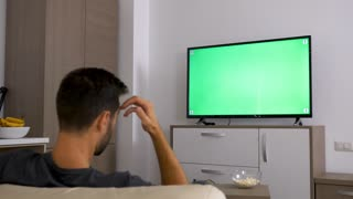 Man watching a big green mock-up screen TV in the living room. Dolly slider 4K footage