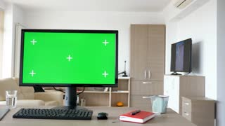 Modern personal computer with big green screen chroma mock up in the living room of comfy house. A man walks in background while the TV is on and sits on the sofa looking at the phone