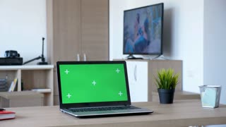 Notebook with isolated green screen mock up in the middle of a living room. A man walks in the room while the TV is on and sits comfortably on the couch