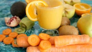 Orange detox smoothie on vivid background next to fresh fruits and vegetables