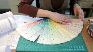 Over top view of architect woman choosing colors from color pallet at her desk. Blusiness woman at her work office