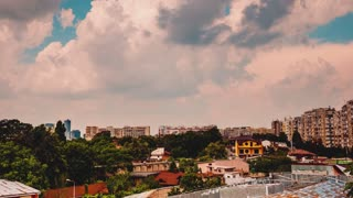 PAN UP timelapse of clouds moving fast over a residential area in the city
