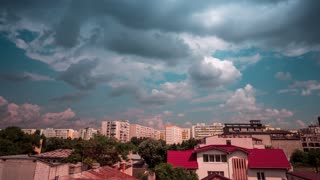 PANNING UP TIMELAPSE of dark stormy rainy clouds moving fast over residential area in the city