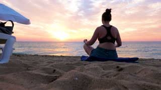 Peace and relaxation while woman is doing yoga on the beach at the sunrise
