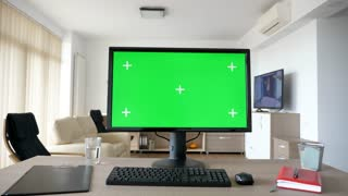Personal PC computer with big green screen chroma mock up on the table in the living room. A guy is entering the room in background while the TV is on and sits on the sofa looking at his phone