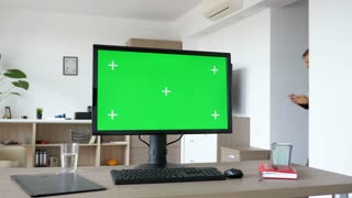 Personal PC with big green screen chroma mock up on the table in the living room. A man walks in the background while the TV is on and sits on the couch looking at his smartphone