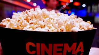 Pop corn in carton box with cinema word written on it in cinema hall