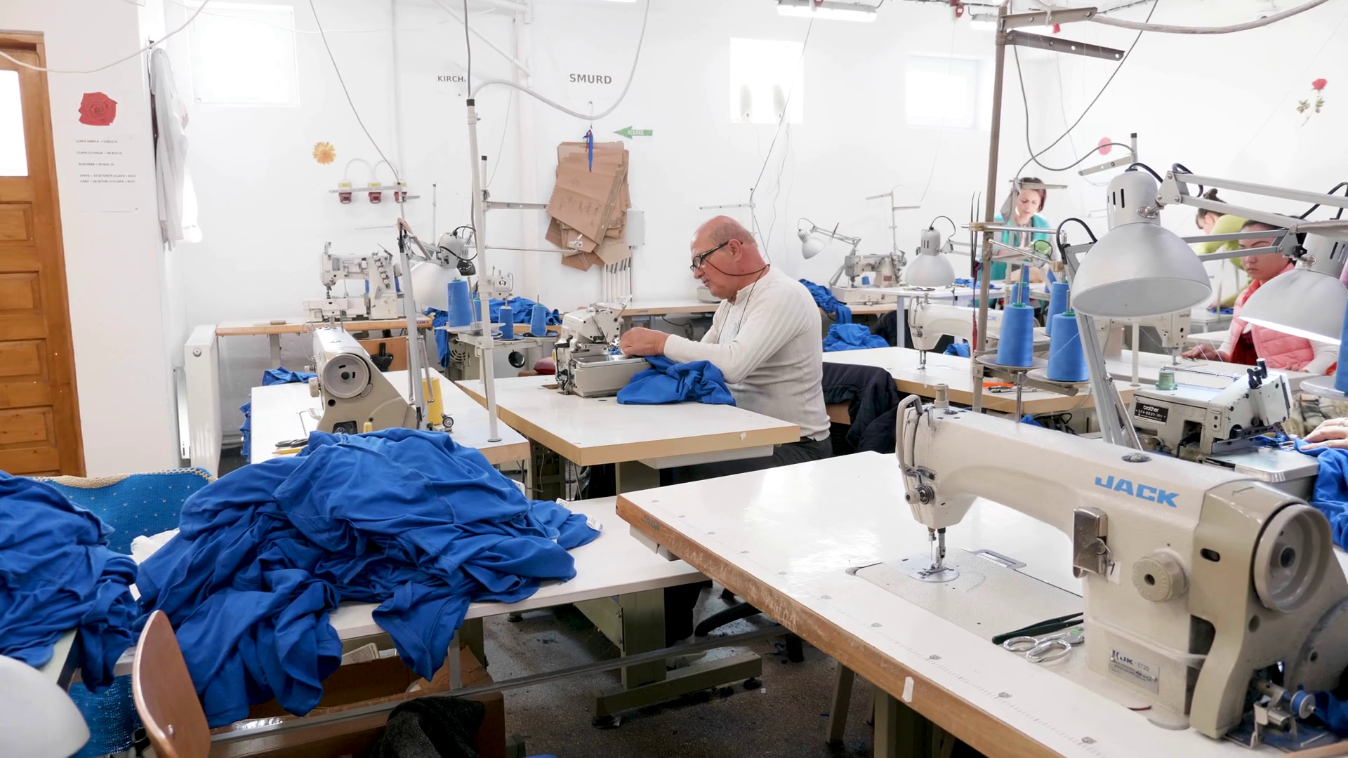 Portrait of a man at a sewing machine in a sewing factory. Textile production. Stock Video Footage - Storyblocks
