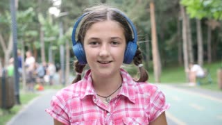 Portrait of cute girl with blue headphones skating in the park. Slow motion footage