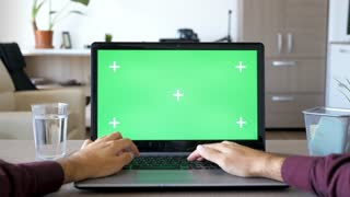 POV of man typing on laptop with green screen chroma mock up. He is in his living room in the house. First person view