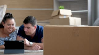 Rack focus young couple surrounded by cardboard boxes is shopping online for furniture. They just moved in new house